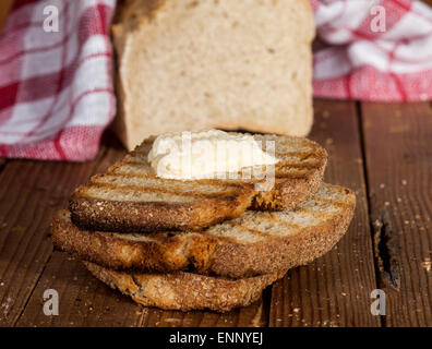 Whole bread and toasted slices of bread with butter on a wooden background. - Stock Photo