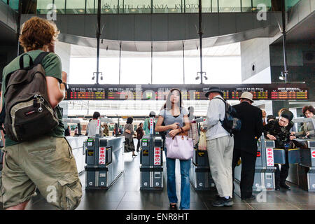 Japan, Kyoto station. Young woman and other busy commuters passing through automatic ticket barriers, low angle - Stock Photo