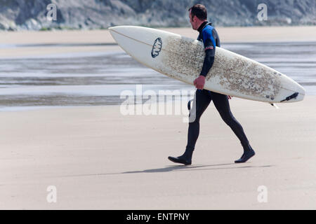 Surfer carrying surf board walking on sandy beach at Whitesands Bay, Pembrokeshire Coast National Park, Wales in - Stock Photo