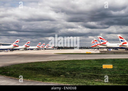 London Heathrow Airport parked near runway with stormy sky - Stock Photo