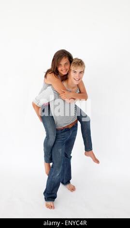 Young boy giving his girlfriend piggyback ride - Stock Photo