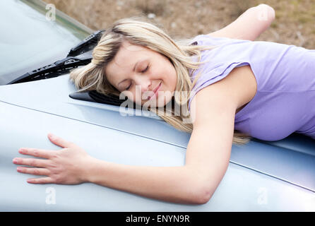 Cheerful female driver huging her new car - Stock Photo