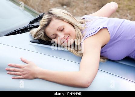 Cheerful female driver huging her new car - Stock Photo