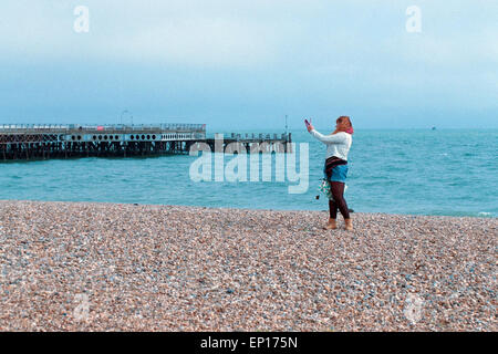 young woman taking a selfie with a tablet on southsea beach england uk - Stock Photo