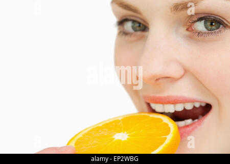 Close up of a woman placing a slice of an orange in her mouth - Stockfoto