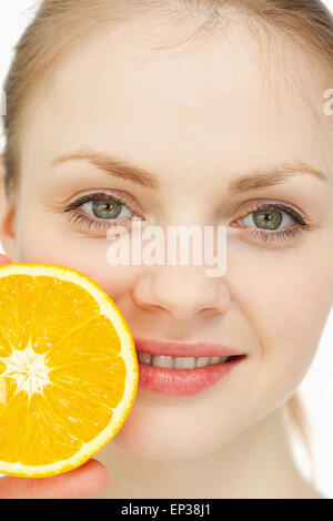 Close up of a woman placing an orange on her lips - Stockfoto