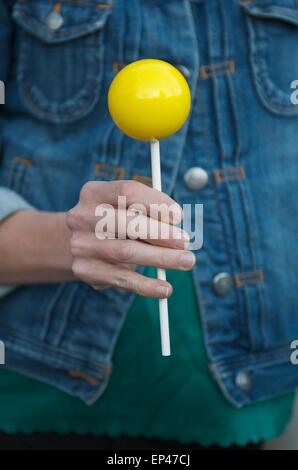 Close up of a woman holding a big yellow lollipop - Stock Photo