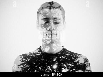 Double exposure portrait of a young man and a tree - Stock Photo