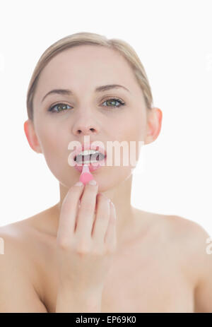 Closeup portrait of young woman applying lipgloss - Stock Photo