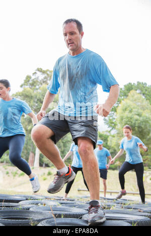 man jumping tire boot camp obstacle course - Stock Photo