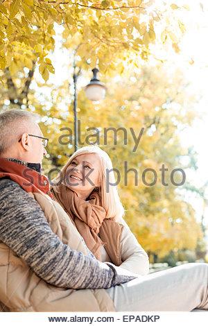 senior adult couple sitting autumn park - Stock Photo