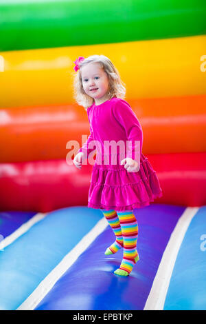 Cute funny preschool little girl playing, jumping and bouncing in an inflatable castle at birthday party on a kids - Stock Photo