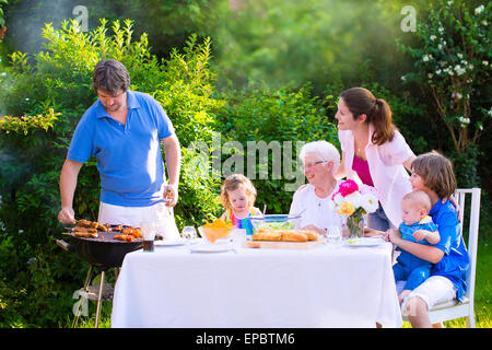 Grill barbecue backyard party. Happy big family enjoying BBQ lunch with grandmother eating grilled meat in the garden - Stock Photo