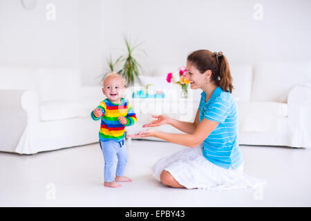 Cute little baby boy making his first steps, walking to his mother in a white sunny living room - Stock Photo