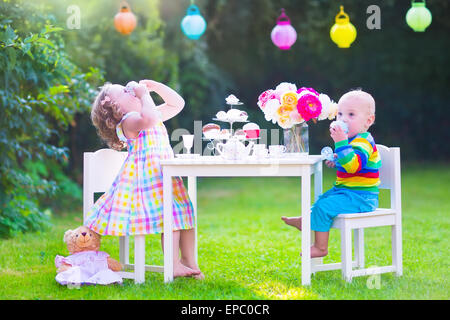 Two happy children, cute curly toddler girl and a little baby boy, brother and sister, enjoying a tea party with - Stockfoto