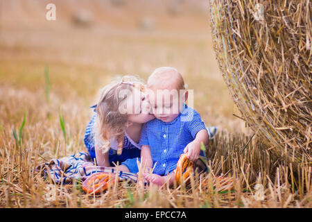 Two children, funny curly toddler girl and a little baby boy, wearing tradtional German costumes playing in a field - Stock Photo