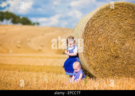 Two children, funny curly toddler girl and a little baby boy, wearing traditional German costumes playing in a field - Stock Photo