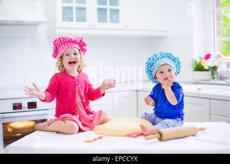 Cute kids, adorable little girl and funny baby boy wearing pink and blue chef hats playing with dough baking a pie - Stock Photo