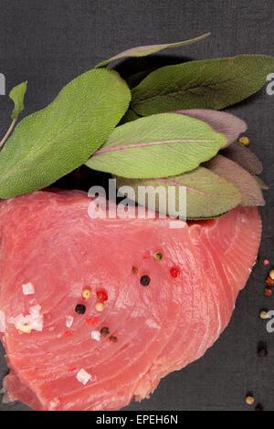 Raw fresh tuna steak with fresh sage herbs, peppercorns and salt on black background, top view. - Stock Photo