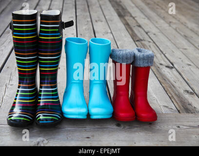 Three pairs of a colorful rain boots - Stock Photo