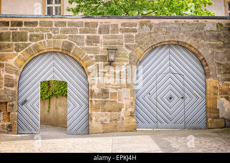 Image with two gates in a wall where a gate is open, the other is closed. - Stock Photo