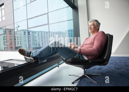Man with coffee cup relaxing in a leather chair at home - Stock Photo