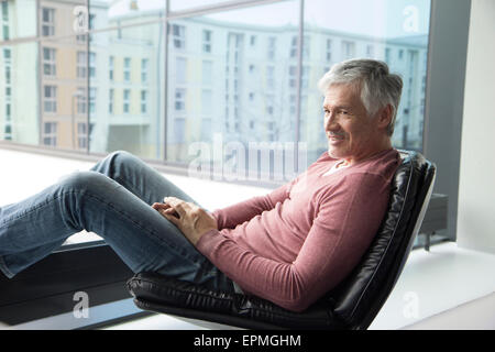 Man relaxing in a leather chair at home - Stock Photo