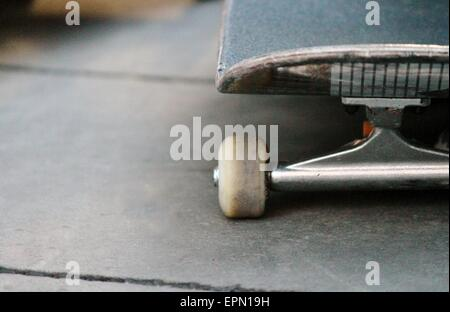 lone skateboard on concrete background with copy space - Stock Photo