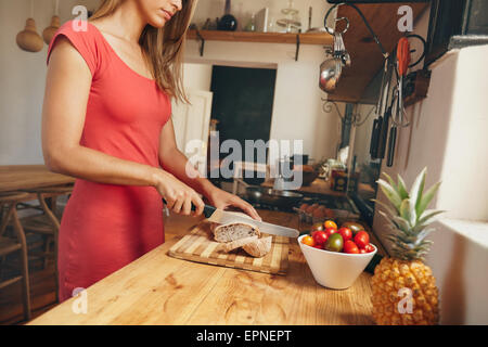Cropped shot of a young woman slicing a fresh baked loaf of bread on a domestic kitchen counter. Female making morning - Stock Photo