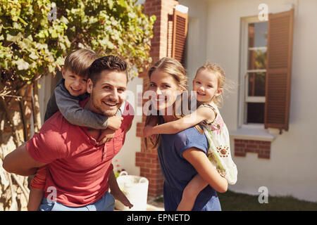 Happy father and mother looking at camera while piggybacking their son and daughter. Happy young family of four - Stock Photo