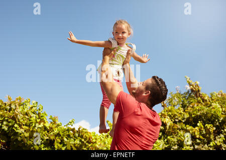Little girl pretending to be a airplane as her father lifts her in the air. Father holding his daughter up high - Stockfoto