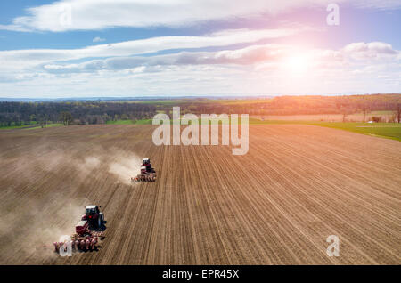 Aerial view of the sunset above the tractor harrowing the large brown field in spring season - Stock Photo