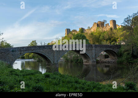 The old stone Dinham Bridge by the River Teme in Ludlow in Shropshire in front of a sunny Ludlow Castle on the hill - Stock Photo