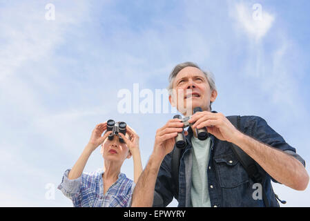 Senior couple watching birds with binoculars - Stock Photo