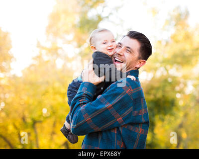 Father hugging baby son (6-11 months) - Stock Photo