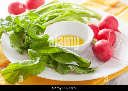 fresh radishes and olive oil on plate - Stock Photo