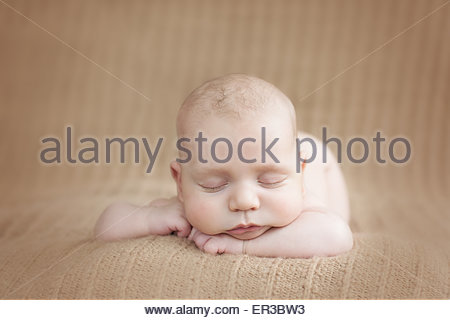 Front view of a baby boy sleeping on a soft blanket - Stock Photo