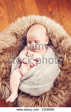 Baby boy sleeping on a fur blanket - Stock Photo