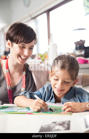 Mother teaching young daughter to read - Stock Photo