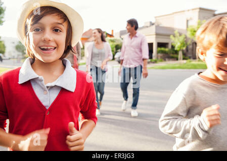 Boys running in street, family walking behind them - Stock Photo