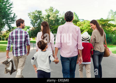 Family walking together outdoors, rear view - Stock Photo
