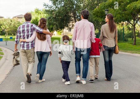 Family walking together in street, rear view - Stock Photo