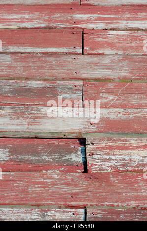 Old wood with peeling brick-red paint. - Stockfoto