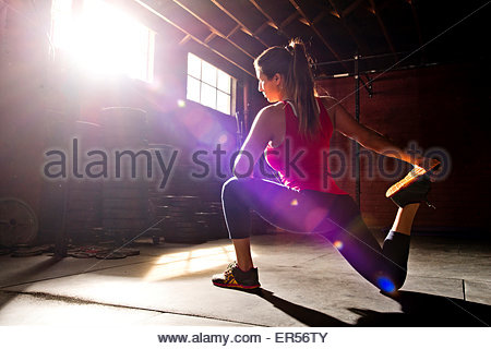 A woman athlete stretches in a crossfit gym. - Stock Photo