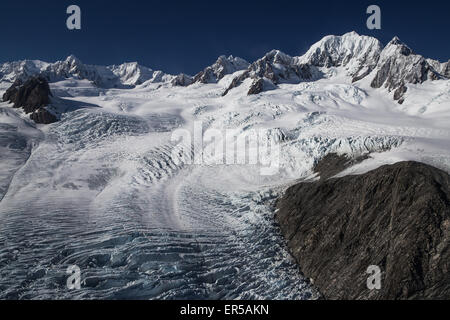 Fox Glacier and Mount Tasman are seen from an aerial perspective along New Zealand's West Coast - Stock Photo