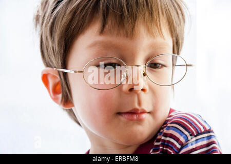 3 - 5 year old Caucasian child, boy. Head and shoulder, facing, indoors, smiling and glancing down, wearing adult - Stock Photo