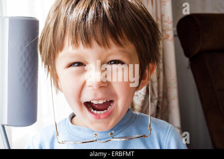 3 - 5 year old Caucasian child, boy. Head and shoulder, facing, indoors, laughing, looks at viewer, wearing glasses - Stock Photo