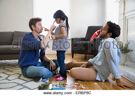 Playful homosexual couple and daughter in living room - Stock Photo