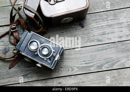 Old retro camera and belt bag (leather case) on vintage wooden boards abstract background - Stock Photo