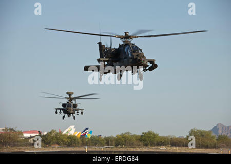 A pair of AH-64D Apache Longbow helicopters taking off on a mission in support of exercise Angel Thunder 2013. - Stock Photo
